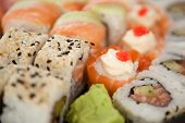 Close-up of assorted sushi set served in white box against white background poster