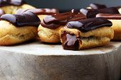 Traditional French Dessert. Eclair With Chocolate Icing. Wooden Background poster