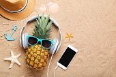 Ripe Pineapple With Sunglasses And Headphones On Beach Sand poster