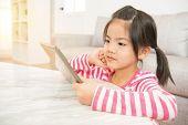 Girl Enjoy Watching Video Cartoon On Pad poster
