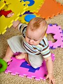 Child jigsaw develops children. Family puzzle making baby. Portrait of boy top view. Playing on floo poster