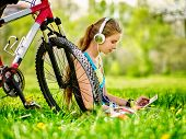 Bikes cycling girl. Girl rides bicycle. Girl wearing headset in cycling watch in pc tablet near bicy poster