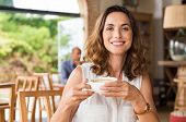 Beautiful smiling woman drinking coffee at cafe. Portrait of mature woman in a cafeteria drinking ho poster