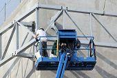 stock photo of cherry-picker  - blue cherry picker in building site in summer  - JPG