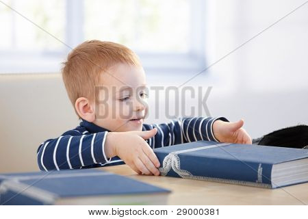 Ginger-haired little boy looking at encyclopedia at table, smiling.?