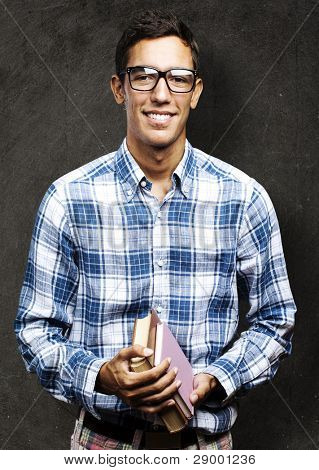 portrait of a handsome young student smiling and holding books against a grunge background