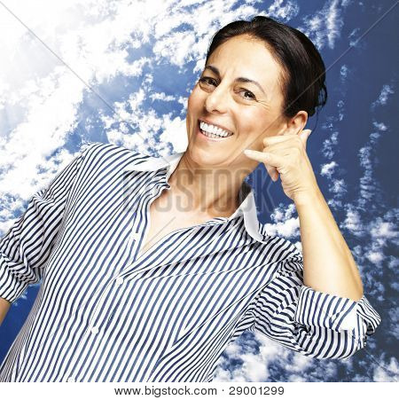 portrait of a middle aged woman gesturing talking on telephone against a cloudy sky