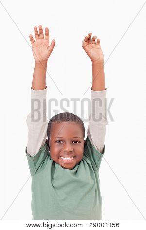 Bildnis eines Knaben erhöhen seine Arme vor einem weißen Hintergrund