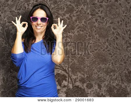 portrait of middle aged woman gesturing good against a vintage wall