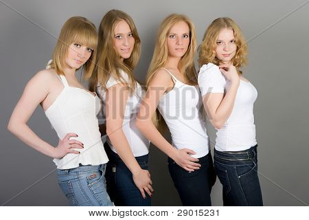 Four attractive girls on a gray background