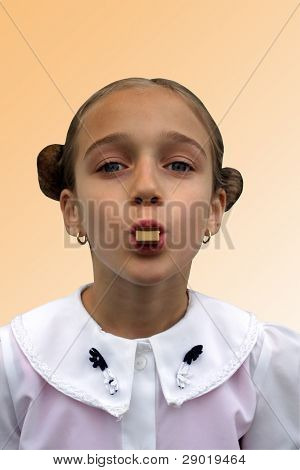 Little girl with chocolate bar in her mouth
