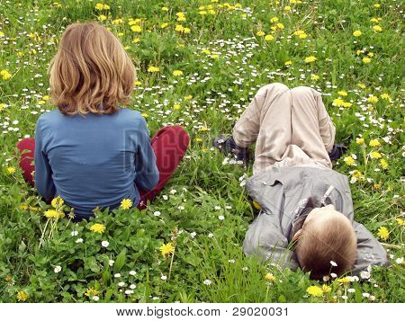 A girl and a boy lying on the grass