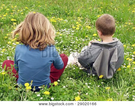 A girl and a boy sitting on the grass