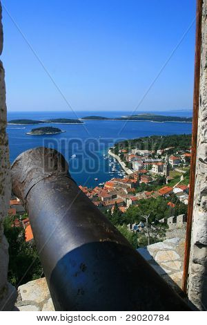 Cannon on the fortress window with aerial view of marina on island Hvar