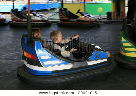 Boy and a girl having a ride in the scooter at the fun fair