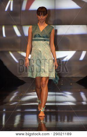 Fashion model in green toned dress walking down the runway