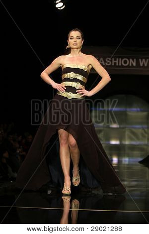 Fashion model in beautiful long dress walking down the runway