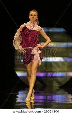 Fashion model in pink silk dress walking down the runway