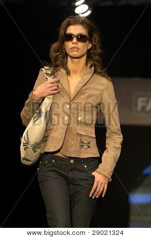 Fashion model with sunglasses and a bag on her shoulder