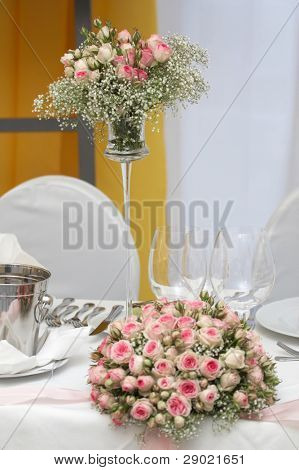 Table set for fine dining during a wedding event. Shallow depth of field, focus on the bouquet of flowers