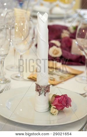 Table set for fine dining during a wedding event. Shallow depth of field, focus on the flower