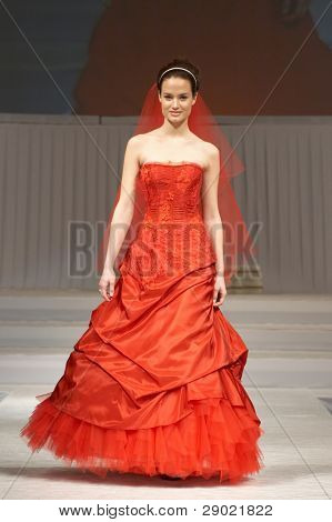 Model in red bridal dress coming down the runway