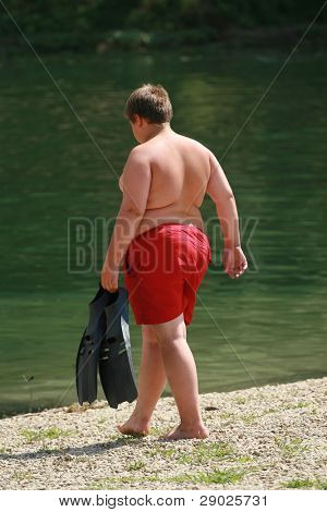 Boy on the beach with obesity problem