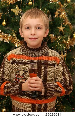 Little boy with glass of non-alcoholic champagne in front of a Christmas tree