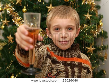 Little boy making a toast with champagne in front of a Christmas tree
