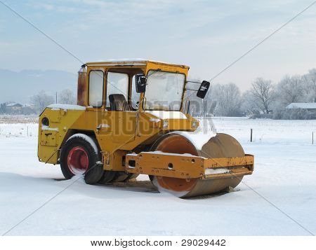 Heavy yellow pneumatic roller compactor under the snow