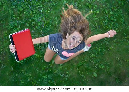 Teenage girl with red laptop jumping up from joy
