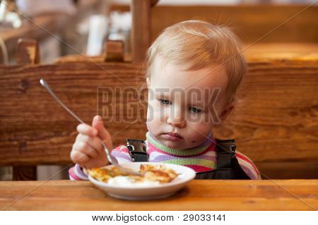 Blond Babe Eats Pancakes At A Wooden Table