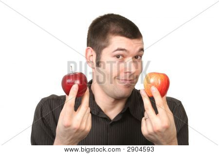 Man Unable To Decide Between Two Apples