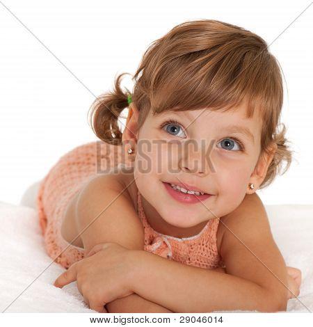 Happy Little Girl On The Bedspread