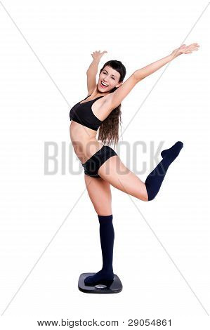 Happy Beautiful Young Woman Dancing Over A Weight Scale.