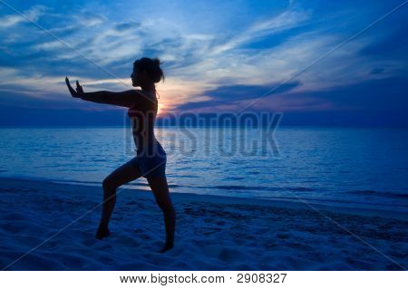 Woman Yogaing By The Sunset Beach
