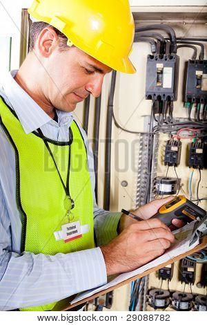 industrial technician recording machine temperature testing result