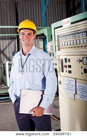 happy male industrial technician inside a factory