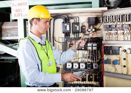 male caucasian electrician checking industrial machine control box temperature