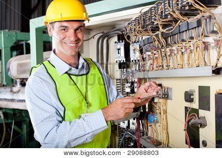 feliz técnico caucásico masculino reparación de caja de control de máquinas industriales