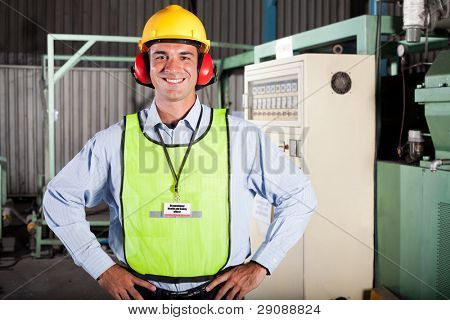 happy male industrial health and safety officer portrait inside factory