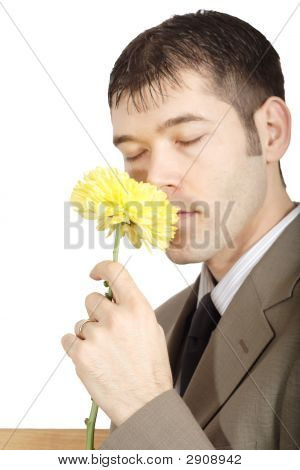 Man Sniffing A Yellow Mum Flower