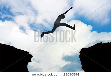 Silhouette Of Man Jumping over Cliff