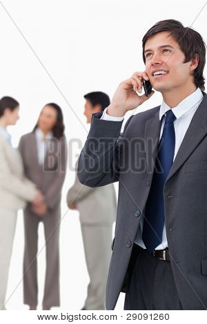 Salesman talking on mobile phone with team behind him against a white background