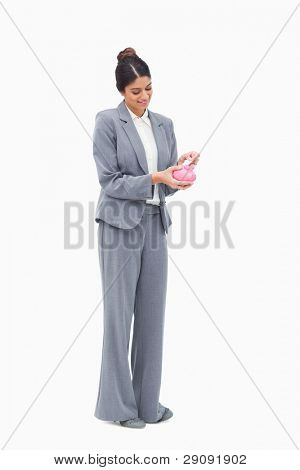 Smiling female banker putting bank note into piggy bank against a white background