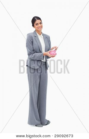 Smiling female banker putting money into piggy bank against a white background