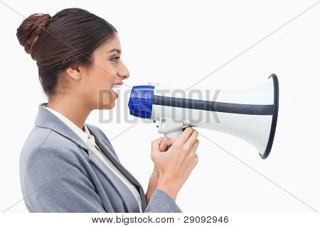 Side view of saleswoman using megaphone against a white background