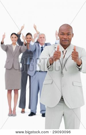 Tradesman with cheering team behind him giving thumbs up against a white background