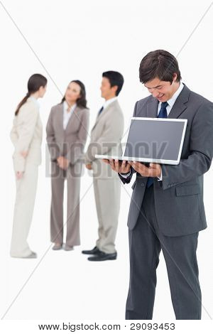 Salesman showing notebook screen with team behind him against a white background