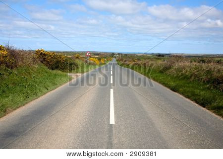 An English Country Road With The Sea On The Horizon.